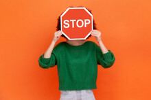 Unknown Woman With Wearing Green Casual Style Sweater Hiding Her Face Behind Red Stop Traffic Symbol, Warning, Avoids Forbidden Actions. Indoor Studio Shot Isolated On Orange Background.