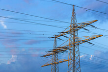 Electricity Pylons Standing Against Blue Cloudy Sky