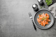 Leinwandbild Motiv Salmon carpaccio with capers, onion and microgreens on grey table, flat lay. Space for text
