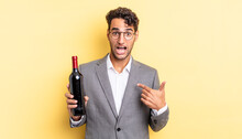 Hispanic Handsome Man Feeling Happy And Pointing To Self With An Excited. Wine Bottle Concept