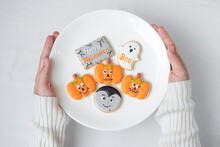 Woman Hand Holding Plate Of Funny Halloween Cookies. Happy Halloween Day, Trick Or Threat, Hello October, Fall Autumn, Traditional, Party And Holiday Concept