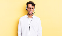 Hispanic Handsome Man Feeling Disgusted And Irritated And Tongue Out. Telemarketer Concept