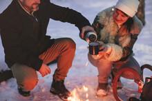 Joyful Happy Family Couple In Love Basking By Campfire Outside In Winter Snowy Forest