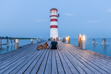 Man With DogWatching Sunrise At Wooden Pier With Lighthouse .  Togetherness And Friendship In Travel