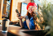 Young Woman Laughing While Holding Smart Phone At Sidewalk Cafe