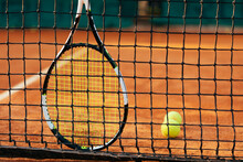 Tennis Racket And Ball By Net At At Sports Court