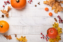 Decor From Pumpkins, Berries And Leaves On White Rustic Wooden Background. Concept Of Thanksgiving Day Or Halloween. Top View Festive Autumn Composition With Copy Space.