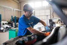 Male Mechanic Repairing Automobile In Workshop