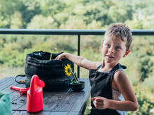 Positive Boy Touching Soil In Flowerpot And Looking At Camera