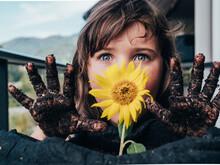 Dirty Girl Having Fun Against Blooming Helianthus Growing In Soil