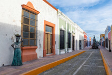 Mexico, Campeche, San Francisco De Campeche, Alley In Historic City With Sculpture Of Woman In Foreground And Christmas Tree In Background