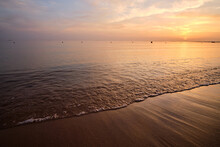 Calm Sea Shore With Crushing Waves On Sandy Beach At Sunrise.