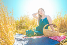 A Blonde Woman With Wicker Basket And Red-white Napkin Sits On A Blue Blanket Among A Wheat Field. Picnic On A Sunny Autumn Day In Nature. High-key Lighting