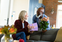 Happy Senior Diverse Couple In Living Room Sitting On Sofa, Giving Flowers And Present