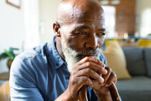 Thoughtful Senior African American Man In Living Room Sitting On Sofa, Holding Walking Cane