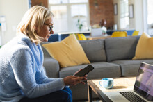 Happy Senior Caucasian Woman In Living Room Sitting On Sofa, Using Smartphone And Laptop