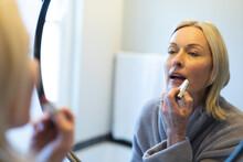 Happy Senior Caucasian Woman In Bathroom, Looking To Mirror, Putting Lipstick On