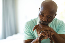 Thoughtful Senior African American Man In Bedroom Holding Walking Cane