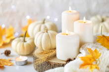 Hello Autumn Or Happy Thanksgiving Concept. White Burning Candles With White Pumpkins At The Background, Knitted Plaid And Autumnal Leaves. Shallow Depth Of Field