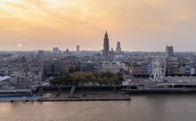 Aerial Sunrise Shot Over The River Scheldt Of Antwerp Cathedral, Boerentoren And Giant Wheel The View Reuzenrad During Beautiful Morning Golden Light