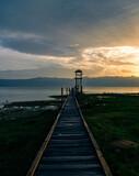 Fototapeta Pomosty - Drewniany pomost nad jeziorem Szkoderskim z widokiem na góry podczas zachodu śłońca