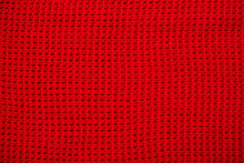 Knitted Surface Of Woolen Things As A Background. Close-up Of Soft Fabric Red Color Knitted Patterns Texture. Warm Winter Clothing. Background Textile Surface With Copy Space For Text.