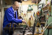 Confident Gunsmith Lubricates And Cleans Barrel Of A Rifled Shotgun