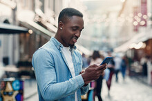 Young African American Man Standing On The Summer Street And Using Smart Phone.