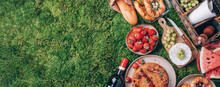 Picnic Straw Basket With Healthy Food, Accessories. Summer Picnic With Cake, Fruits, Cheese, Wine And Snacks On Plaid Over Green Background. Top View. Copy Space. Summer Family Lunch. Romantic Picnic