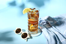 Glass Of Refreshing Long Island Iced Tea, Sunglasses And Towel On Color Background