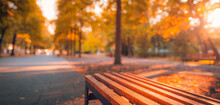 Fall Park Bench Autumn Urban Landscape Recreation. Peaceful Relaxing Sunset Closeup Of Wooden Bench With Blurred Bokeh Forest Tress, Sun Rays. Idyllic Seasonal Nature Concept, Dreamy October Landscape