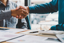 Business Handshake In The Office Meeting,  Financing Accounting Concept.  Businessman Investment Consultant Analyzing Company Financial Report Balance Sheet Statement Working With Digital Graphs.