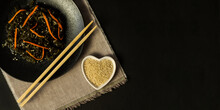 Seaweed Salad With Sesame Seeds In A Black Plate With Chopsticks. Black Background. Japanese Or Chinese Kelp Salad. View From Above. Vegan Asian Food.