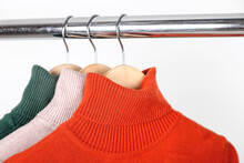 Basic Autumn Women's Wardrobe Concept. Blank Turtleneck Sweaters On Clothes Hanger. Bright Orange Ocher Roll-neck With Beige And Green.