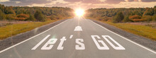 Word Let's Go Written On Highway Road In The Middle Of Empty Asphalt Road At Beautiful Sunset Sky. Concept For Business Planning, Strategy And Challenge Or Career Path, Opportunity And Change