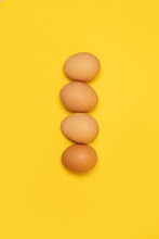 Tasty Brown Chicken Eggs And One Broken Egg With Yolk On Yellow Background
