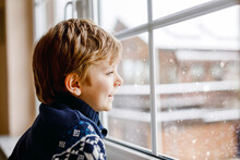 Happy Adorable Kid Boy Sitting Near Window And Looking Outside On Snow On Christmas Day Or Morning. Smiling Healthy Child Fascinated Observing Snowfall And Big Snowflakes