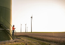 Male Technican Looking At Wind Turbine While Standing On Staircase