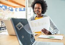 Smiling Female Freelancer Analyzing Business Plan At Desk