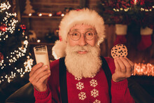 Photo Of Charming Sweet Mature Man Dressed Santa Costume Smiling Holding Milk Glass Tasty Biscuit Indoors Home Room
