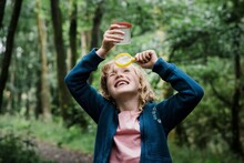 Girl Looking Through A Magnifying Glass At Bugs In The Forest