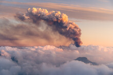 Sea Of Clouds Next To Smoke From A Volcano