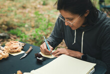 Woman Writing Names Of Mushrooms On Paper