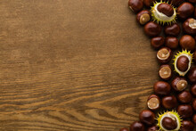 Fresh Chestnuts On Dark Brown Wooden Table Background. Closeup. Empty Place For Inspirational Text, Quote Or Sayings. Top Down View.