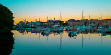 Tranquil Sunrise Seascape With Moored Boats And Yachts At The Marina In Woods Hole, Massachusetts. Blue Ocean And Sky With Orange Reflections Of The Daybreak.