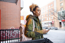 Beautiful Young Woman In Camouflage Jacket With Headphones In City