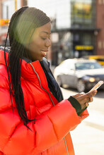Young Woman In Red Coat Using Smart Phone On Sunny City Street