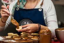 Cropped View Of An Unrecognizable Female Cook Making Argentine Alfajores By Putting Dulce De Leche Into Dough Lids