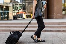 Saleswoman Walking With Wheeled Baggage On Sidewalk