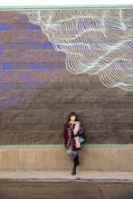 Stylish Woman Standing At Urban Brick Wall With Wave Graffiti